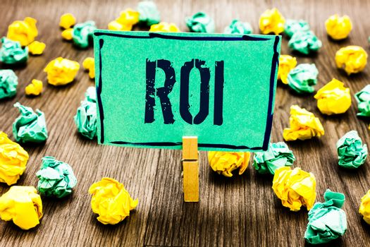 Conceptual hand writing showing Roi. Business photo showcasing Return on investment performance measure gains business growth Crumpled papers ideas mistakes paperclip clip objects wood