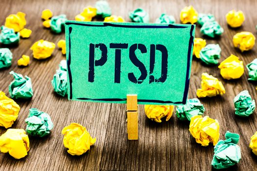Conceptual hand writing showing Ptsd. Business photo showcasing Post Traumatic Stress Disorder Mental Illness Trauma Fear Depression Crumpled papers ideas mistakes paperclip clip objects wood