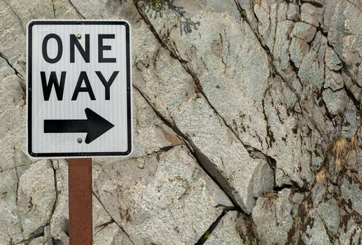 One Way highway road sign against grunge texture rock wall
