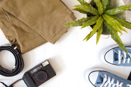 Brown pants, camera and shoes Travel accessories on a white background.