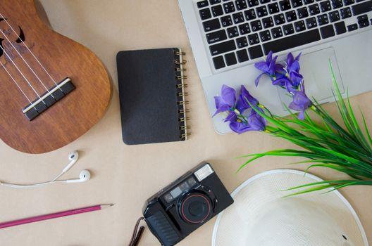 Laptops and cameras ukulele and purple flowers
