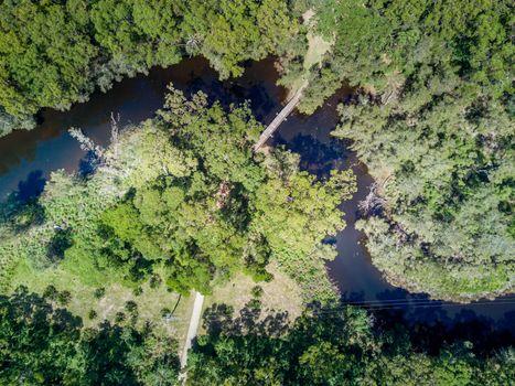 Timber bridge crosses a winding creek through gum tree forest.  Durras Creek Australia