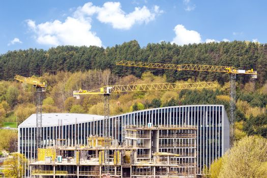 Panoramic view of industrial construction site with cranes in the background of green hills