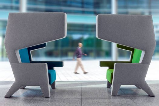 Two modern empty armchairs in waiting hall with interior walking blury man in the background