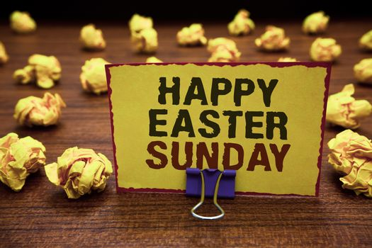 Handwriting text writing Happy Easter Sunday. Concept meaning Greeting someone about holidays Spring is coming Yellow sticky card clipped text notice crumpled paper balls wood table