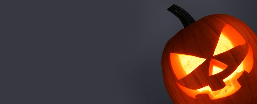 Funny glowing Halloween Pumpkin on gray background