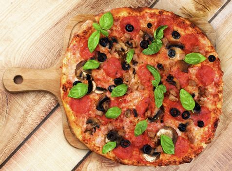 Homemade Pepperoni Pizza with Mushrooms, Black Olives, Ham and Basil on Wooden Cutting Board on Wooden background. Top View