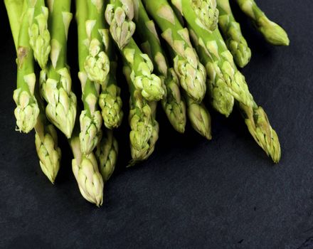 Heap of Fresh Asparagus Sprouts closeup on Black Slate background