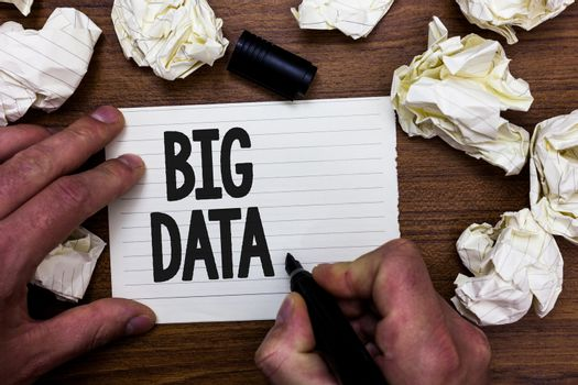 Word writing text Big Data. Business concept for sets that so complex that traditional software cant deal with them Man holding marker notebook page crumpled papers several tries mistakes