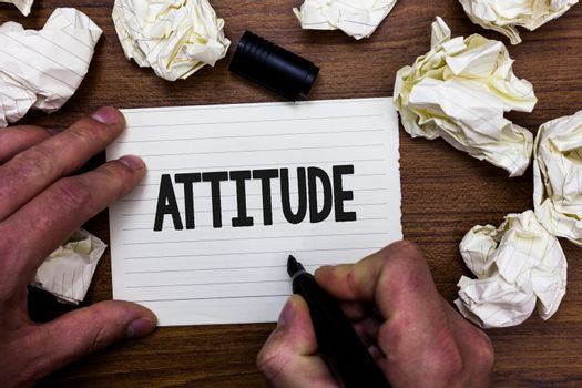 Word writing text Attitude. Business concept for settled way of thinking or feeling about something Personality Man holding marker notebook page crumpled papers several tries mistakes