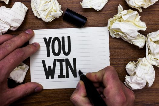 Word writing text You Win. Business concept for be first in school race or competition Got gold medal Rating Man holding marker notebook page crumpled papers several tries mistakes