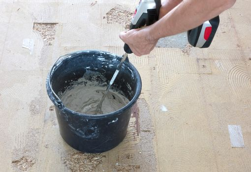Man is mixing grey concrete and prime in the bucket.