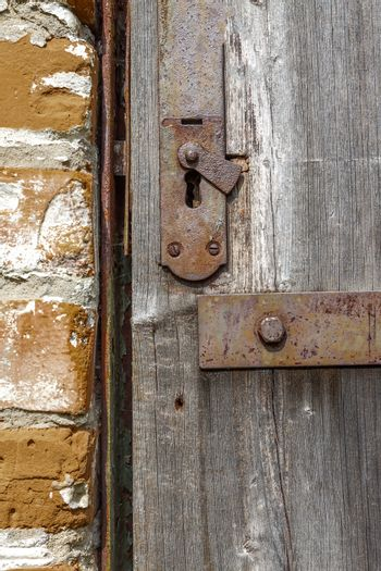 Keyhole in an old paneled wooden door; rusty and weathered. This
