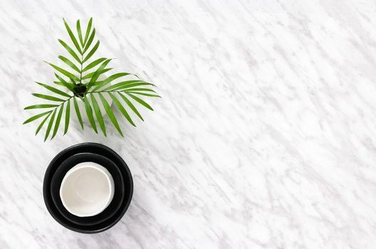 Ceramics and palm leaves on marble background