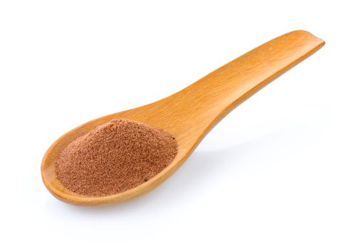 malt extract in wood spoon on white background