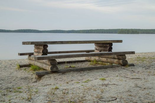 Wooden Bench by Lake with a cloudy sky and forest.