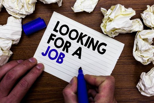 Writing note showing Looking For A Job. Business photo showcasing Unemployed seeking work Recruitment Human Resources Hand holding marker write words paper lob scatter around woody desk