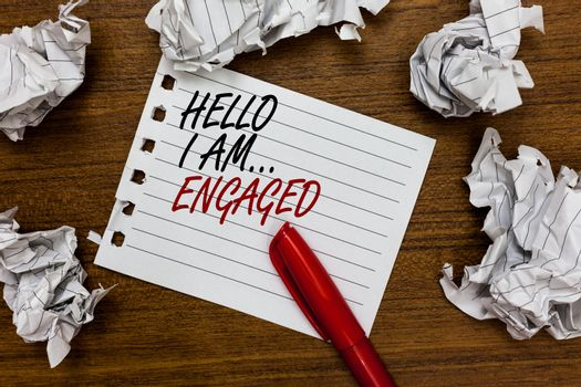 Conceptual hand writing showing Hello I Am... Engaged. Business photo showcasing He gave the ring We are going to get married Wedding Written white page touched red marker scattered paper lump