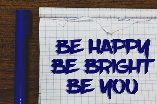 Writing note showing Be Happy Be Bright Be You. Business photo showcasing Self-confidence good attitude enjoy cheerful Written white notepad on grey wooden background beside blue marker