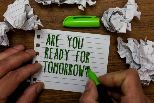 Word writing text Are You Ready For Tomorrow question. Business concept for Preparation to the future Motivation Hand hold green pen and words on white page paper lobs around on wooden desk