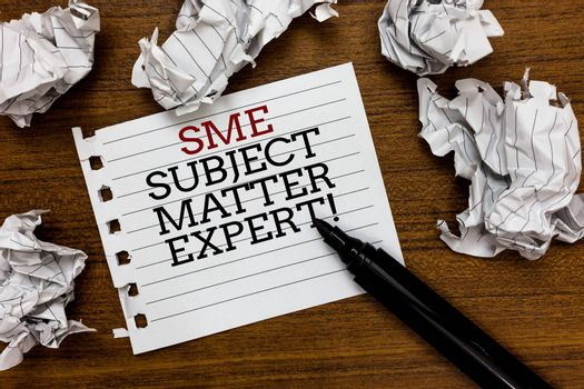 Text sign showing Sme Subject Matter Expert. Conceptual photo Authority in a particular area or topic Domain Paper lumps laid randomly around white notepad touch black pen on woody floor