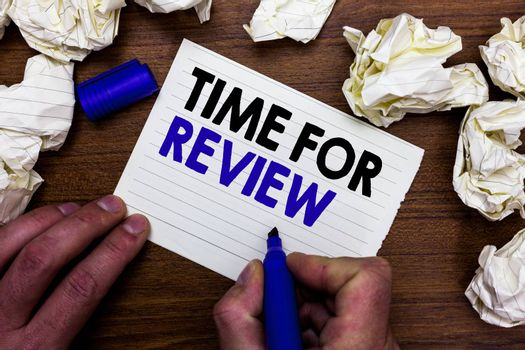 Writing note showing Time For Review. Business photo showcasing Evaluation Feedback Moment Performance Rate Assess Hand holding marker write words paper lob scatter around woody desk