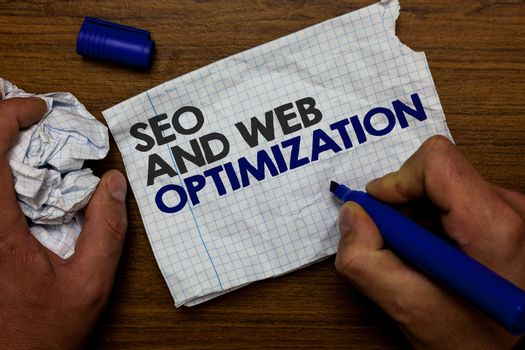 Word writing text Seo And Web Optimization. Business concept for Search Engine Keywording Marketing Strategies Hand hold paper lob and blue marker wooden base with torn white written page