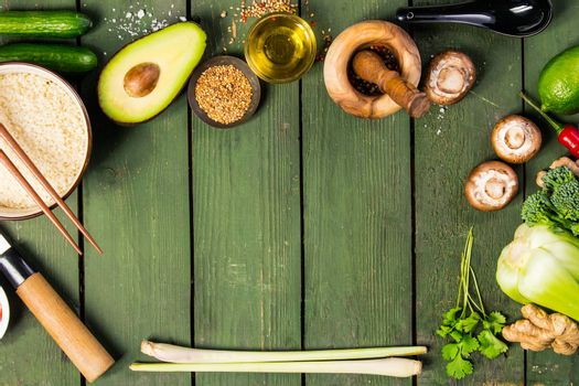 Asian cuisine ingredients on wooden background, top view. Vegetables, spices, shrimp, noodles, rice, sauces for cooking vietnamese, thai or chinese food. Clean eating food concept