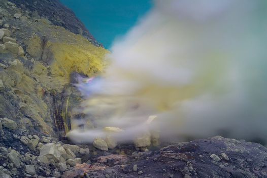 Blue sulfur flames and Sulfur fumes from the crater of Kawah Ijen Volcano in Indonesia.