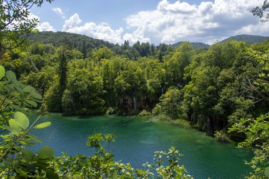 Landscape in Plitvice with green trees, a blue lake and a blue sky with clouds on a sunny day.