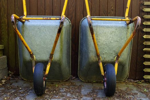 Two wheelbarrows standing in front of wooden wall outside.