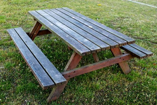 Wooden table bench standing on grass on football field in summer.