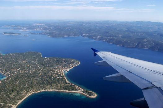 Airplane wing and Croatia land in summertime on a sunny day.
