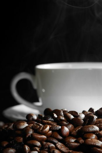 Cup of steaming coffee on coffee beans on black background