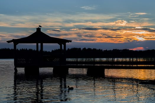 Gazebo in Lake with Mallard Duck in Water at Sunset.