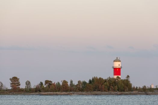 Light House with trees and Ocean with a cloudy sky.