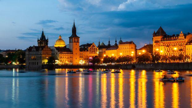 Historical buildings of Smetana Embankment reflected in the water of Vltava River on summer evening. Prague, Czech Republic