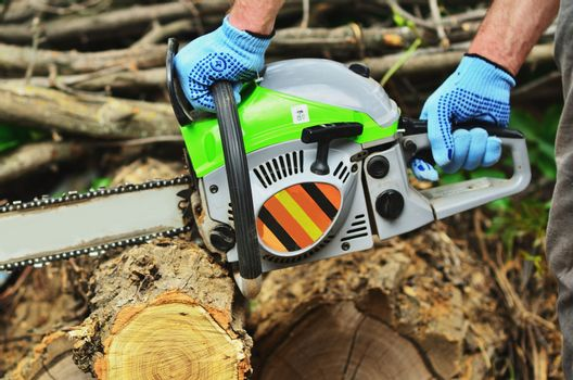 A man in working gloves works chainsaw