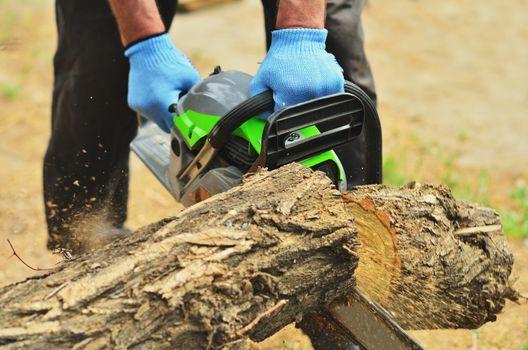 A man saws a log chainsaw, a piece of deck