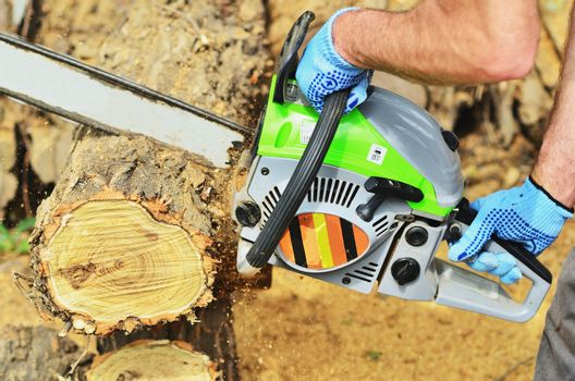 A man saws a piece of a large pack of chainsaw