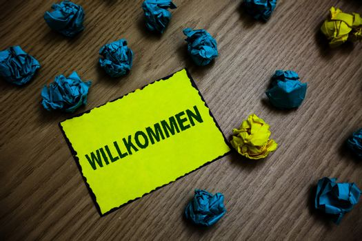 Word writing text Willkommen. Business concept for welcoming people event or your home something to that effect Yellow piece paper reminder lots crumpled papers several tries wooden floor