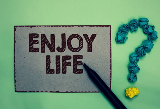 Word writing text Enjoy Life. Business concept for Any thing, place,food or person, that makes you relax and happy Gray paper marker crumpled papers forming question mark green background