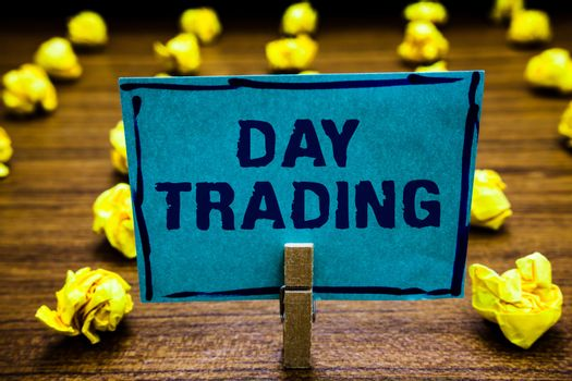 Word writing text Day Trading. Business concept for securities specifically buying and selling financial instruments Clothespin holding blue paper note crumpled papers several tries mistakes