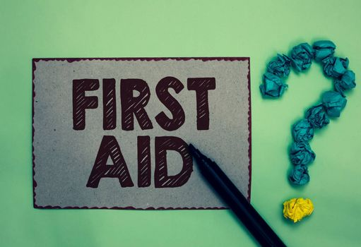 Word writing text First Aid. Business concept for Practise of healing small cuts that no need for medical training Gray paper marker crumpled papers forming question mark green background
