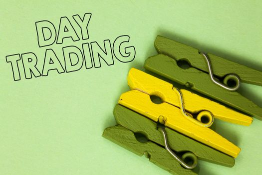 Text sign showing Day Trading. Conceptual photo securities specifically buying and selling financial instruments Three green yellow vintage clothespins clear background Holding things.
