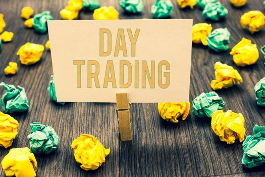 Handwriting text writing Day Trading. Concept meaning securities specifically buying and selling financial instruments Clothespin holding light pink note paper crumpled papers several tries.