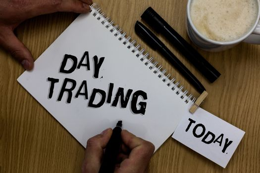 Writing note showing Day Trading. Business photo showcasing securities specifically buying and selling financial instruments Man holding marker notebook clothepin reminder wooden table cup coffee.