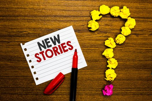 Handwriting text New Stories. Concept meaning imaginary or real people and events told for entertainment Paper marker crumpled papers forming question mark wooden background