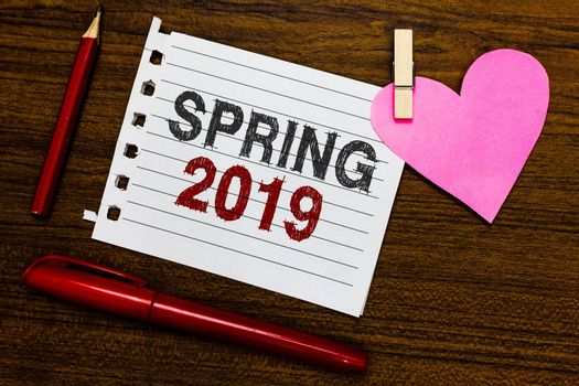 Word writing text Spring 2019. Business concept for time of year where flowers rise following winter season Notebook piece paper markers clothespin holding heart wooden background