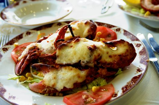 Delicious Grilled Lobster Covered with Fried Cheese on Vegetables Saute Serving on Restaurant Table with Silver Fork and Knife closeup